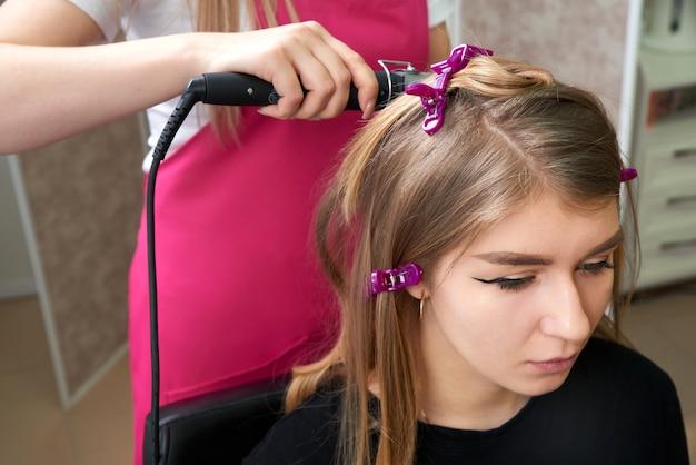 Cabeleireiro faz penteado garota com cabelo comprido em um salão de beleza. crie cachos com ferros de ondulação