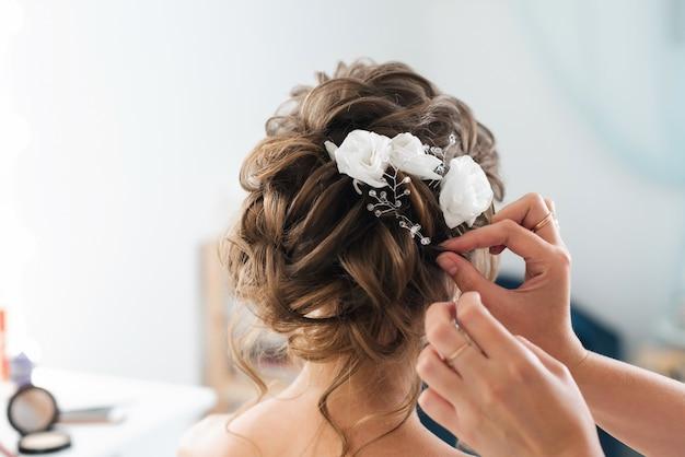 Cabeleireiro faz um penteado elegante estilo noiva com flores brancas no cabelo