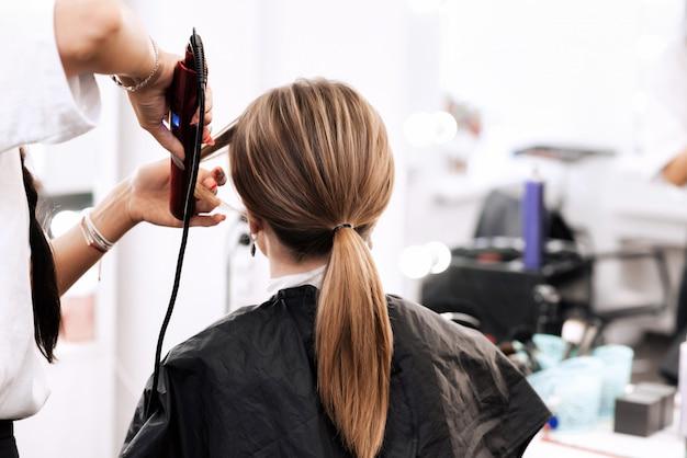 Cabeleireiro faz um penteado na cauda para uma mulher com cabelos castanhos compridos