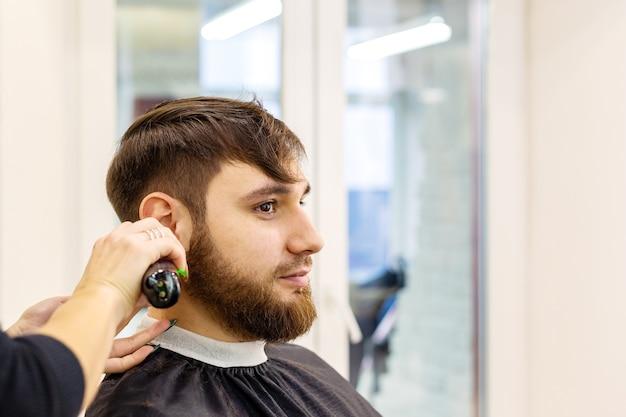 Cabeleireiro fazendo corte de cabelo para cliente do sexo masculino, homem com barba, usando ferramentas profissionais de cabeleireiro