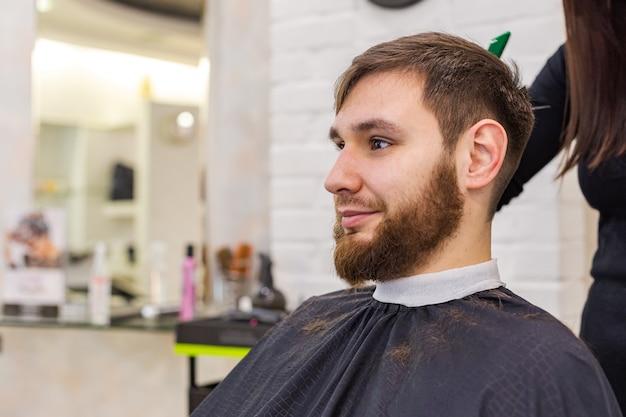 Cabeleireiro, fazendo o corte de cabelo para cliente masculino, homem com barba, usando ferramentas de cabeleireiro profissional