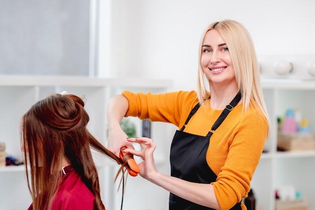 Cabeleireiro fazendo penteado com cachos para jovem modelo usando um ferro de cabelo e sorrindo