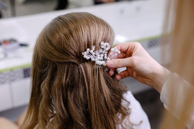 Cabeleireiro fazendo penteado de casamento para mulher de cabelos loiros com cabelos longos no salão de beleza. vista traseira do penteado com gancho de cabelo