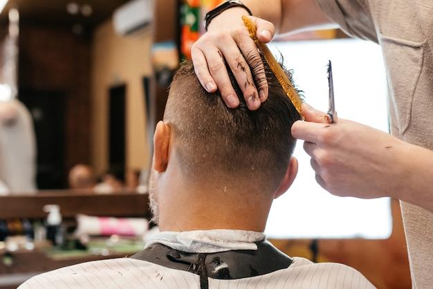 Cabeleireiro fazendo penteado e estilo com tesoura e pente