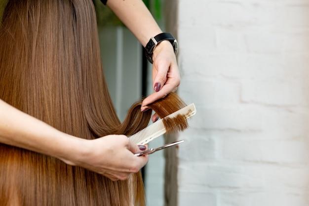 Cabeleireiro, fazendo um corte de cabelo no salão de beleza.