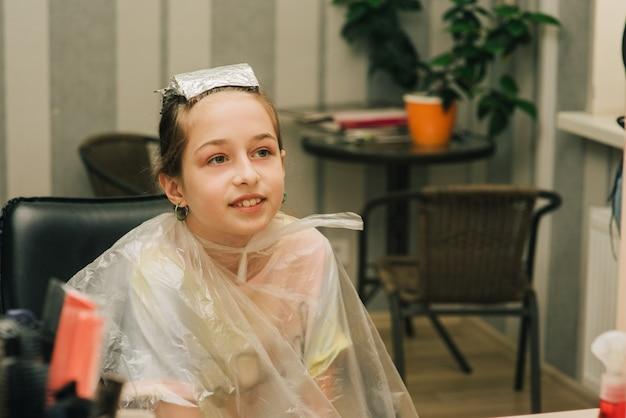 Cabeleireiro fazendo um penteado para uma menina bonitinha. uma adolescente tem a franja iluminada em um salão de beleza. franja laranja. a tendência de cabelos brilhantes.