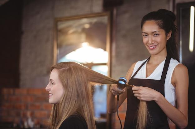 Cabeleireiro feminino alisando os cabelos de um cliente