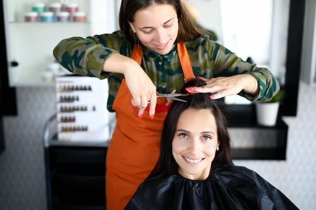Cabeleireiro feminino corta o retrato do cliente mulher