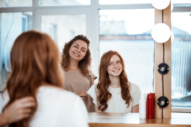 Cabeleireiro feminino e mulher sorrindo, olhando no espelho no salão de beleza