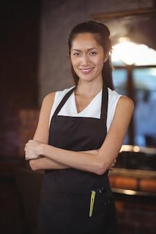 Cabeleireiro feminino em pé com o braço cruzado em um salão de beleza
