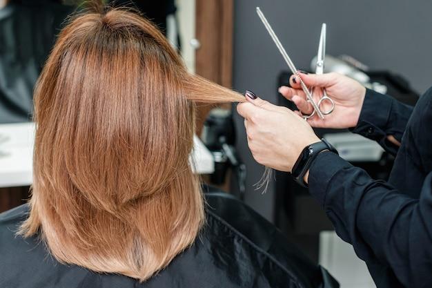 Cabeleireiro feminino faz o penteado de mulher.