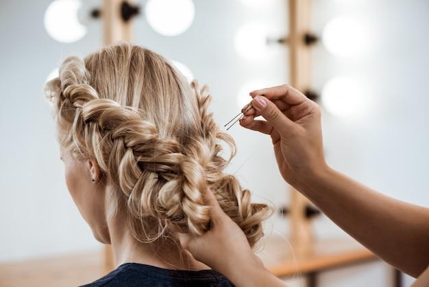 Cabeleireiro feminino fazendo penteado para mulher loira no salão de beleza
