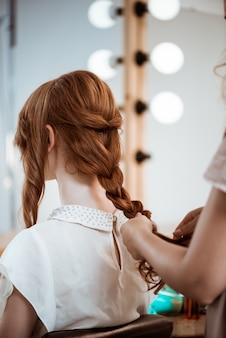 Cabeleireiro feminino fazendo penteado para mulher ruiva no salão de beleza