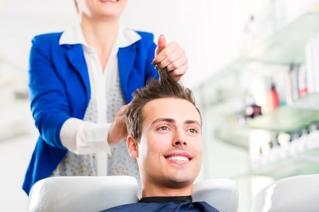 Cabeleireiro feminino lavando cabelo de homem em cabeleireiro