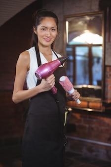 Cabeleireiro feminino segurando a escova e secador de cabelo