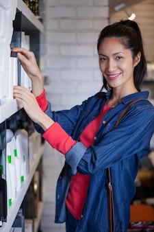 Cabeleireiro feminino sorridente, selecionando o xampu da prateleira em um salão de beleza