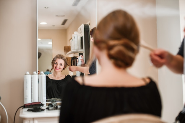 Cabeleireiro, fixação de cabelo de mulher com spray de cabelo