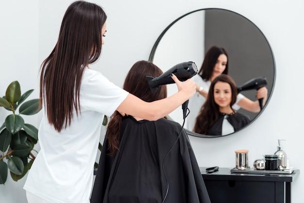 Cabeleireiro focado trabalha secando o cabelo de um cliente bonito