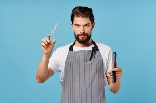 Cabeleireiro fofo com barba segura uma tesoura e um pente em seu modelo de barbearia de penteado de mãos.