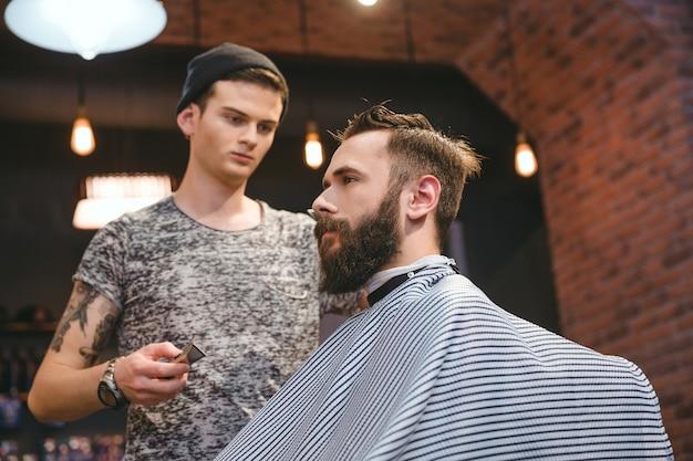 Cabeleireiro habilidoso e concentrado cortando o cabelo de um jovem bonito barbudo na barbearia