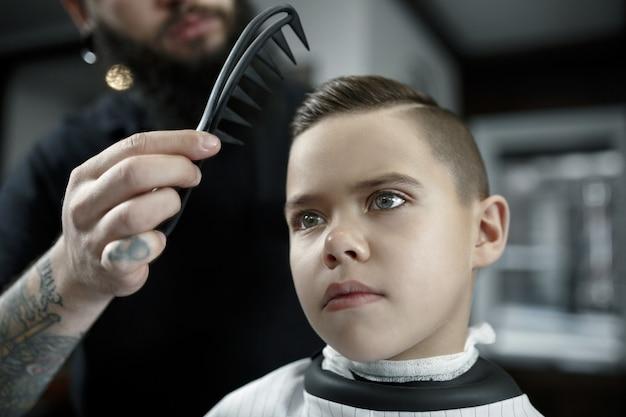 Cabeleireiro infantil cortando menino em uma barbearia