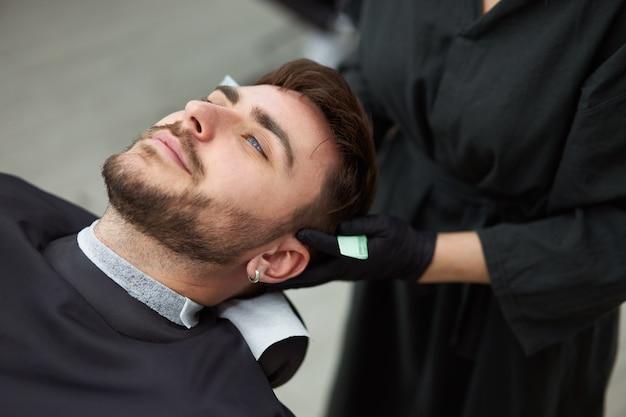 Cabeleireiro jovem e linda mulher caucasiana corta barba de homem bonito na barbearia moderna