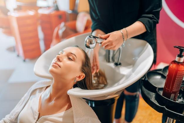 Cabeleireiro lava o cabelo do cliente na bacia, salão de cabeleireiro.