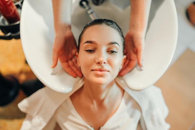Cabeleireiro lava o cabelo do cliente na bacia, vista superior