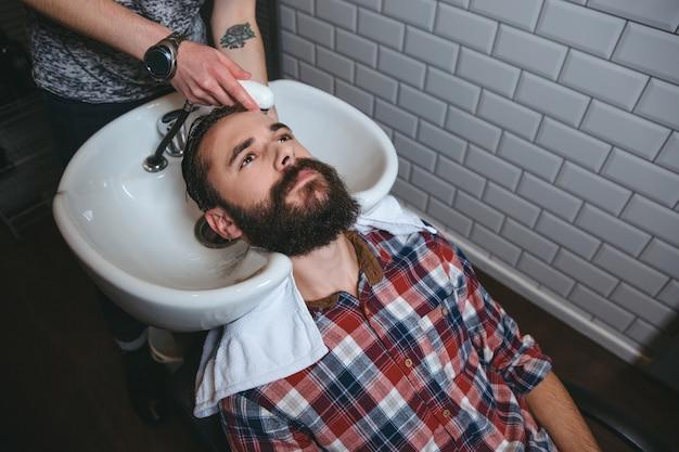 Cabeleireiro lavando cabelo de jovem atraente com barba em uma camisa quadriculada em salão de cabeleireiro