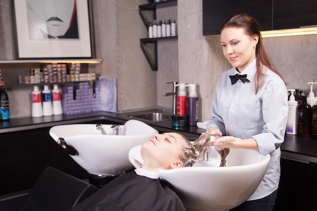 Cabeleireiro lavando cabelo loiro de uma mulher no salão