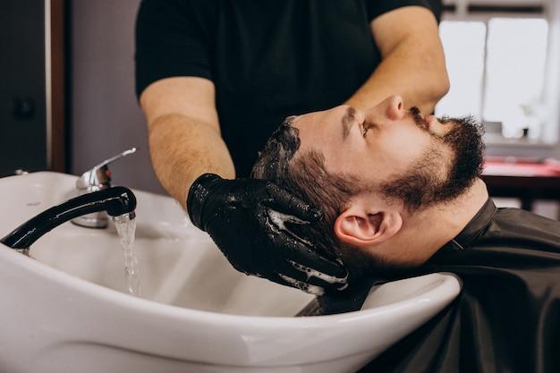 Cabeleireiro, lavando o cabelo de um cliente em uma barbearia