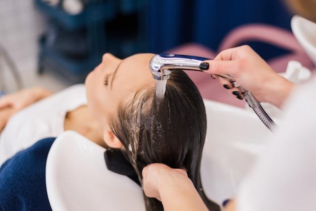 Cabeleireiro lavando o cabelo de uma cliente do sexo feminino com um banho no salão aplicando shampoo condicionador nos cabelos