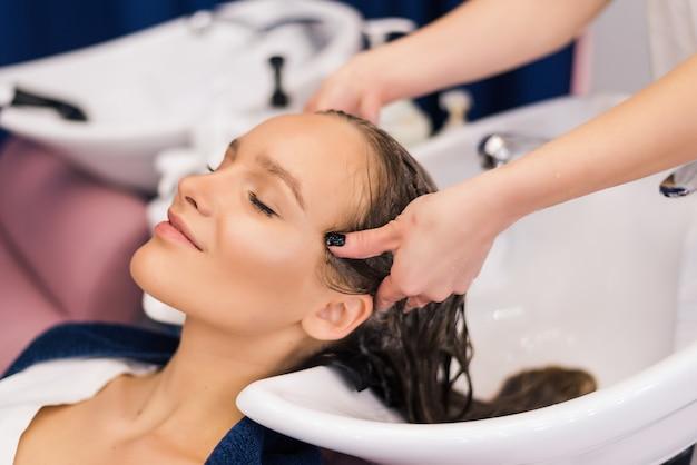 Cabeleireiro lavando o cabelo de uma jovem feliz. menina e fazer massagem relaxante no salão de beleza