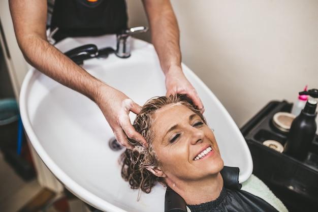 Cabeleireiro lavando o cabelo de uma linda mulher madura em salão de cabeleireiro.