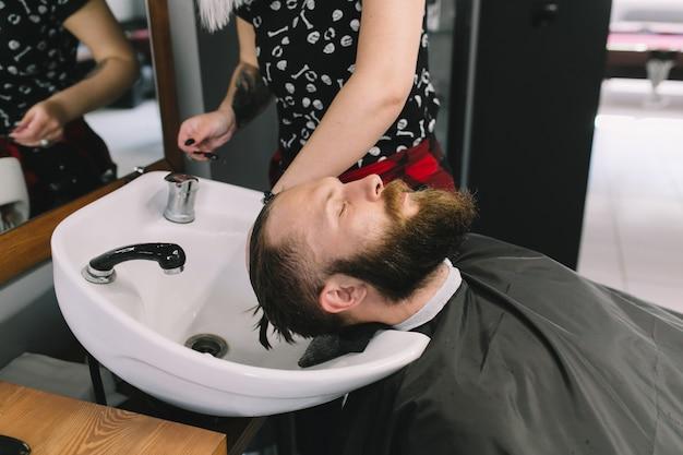 Cabeleireiro lavando o cabelo do cliente na barbearia.