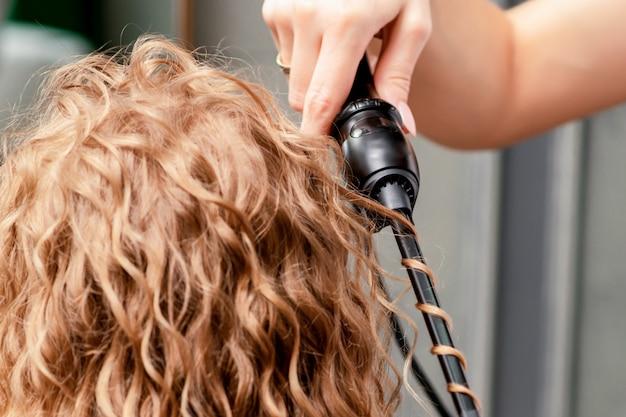 Cabeleireiro mãos enrolar cabelo