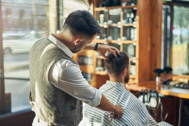 Cabeleireiro masculino concentrado em pé atrás de seu cliente e olhando para seu cabelo enquanto o estiliza