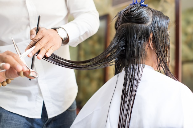 Cabeleireiro masculino cortando cabelos molhados do cliente feminino