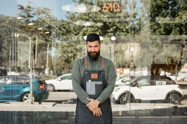 Cabeleireiro masculino em pé perto de barbearia com paredes de vidro