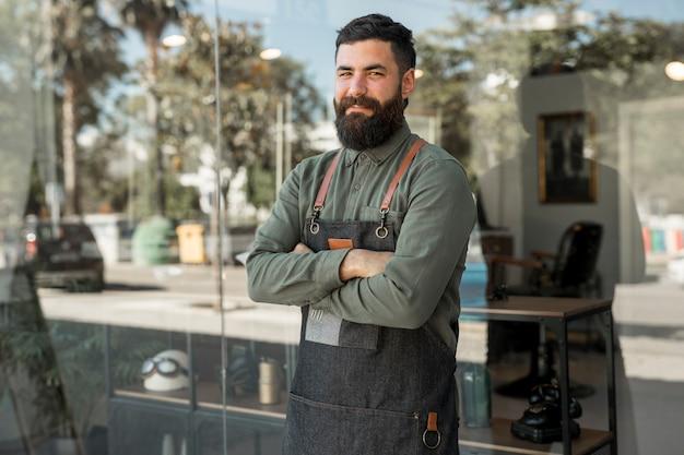 Cabeleireiro masculino hipster em pé perto de barbearia