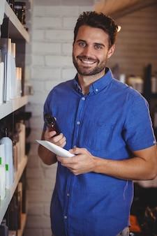 Cabeleireiro masculino sorridente, selecionando o xampu da prateleira em um salão de beleza