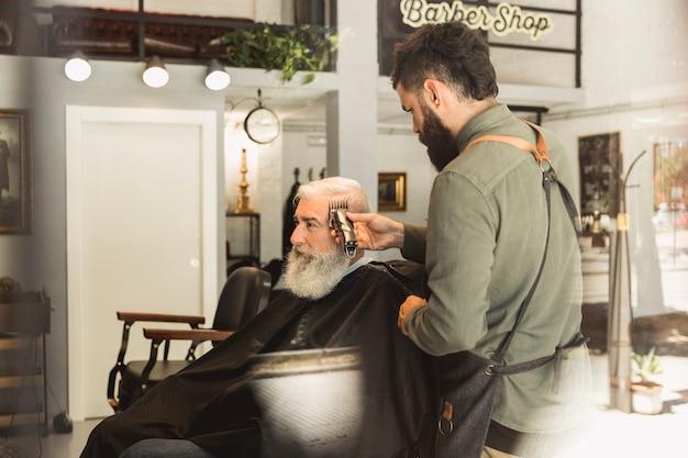 Cabeleireiro masculino trabalhando com cabelo de cliente idoso