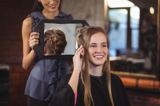 Cabeleireiro, mostrando a mulher o corte de cabelo no espelho