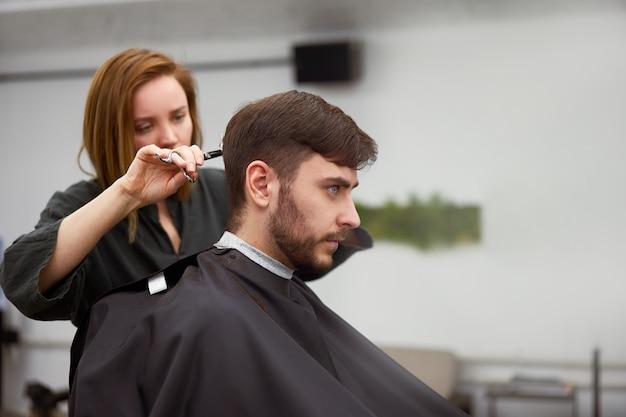 Cabeleireiro mulher cortar cabelo bonito homem caucasiano na barbearia moderna
