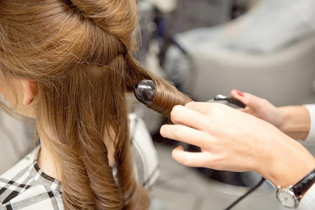 Cabeleireiro mulher fazendo penteado para menina loira no salão de beleza.