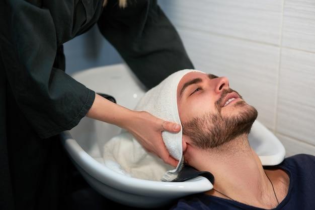 Cabeleireiro mulher lavar cabelo homem bonito caucasiano na barbearia moderna