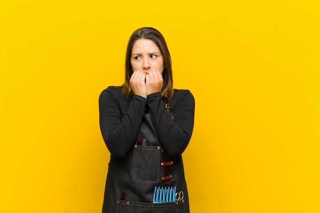 Cabeleireiro mulher olhando preocupado, ansioso, estressado e com medo, roer unhas e olhando para copyspace lateral contra laranja