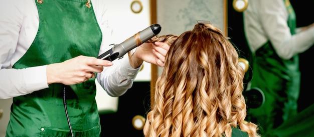 Cabeleireiro ondulando o cabelo com modelador