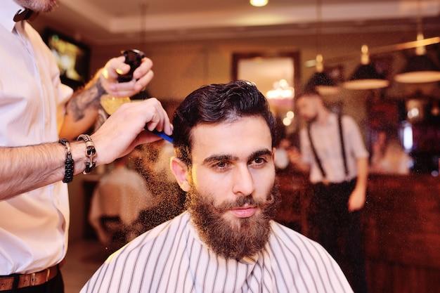 Cabeleireiro ou barbeiro faz um penteado para o cliente no plano de fundo da barbearia moderna