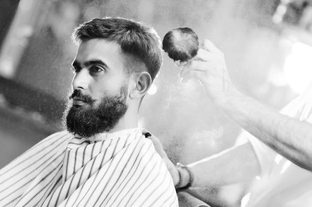 Cabeleireiro ou barbeiro faz um penteado para um jovem homem com barba e bigode e derrama talco no cabelo